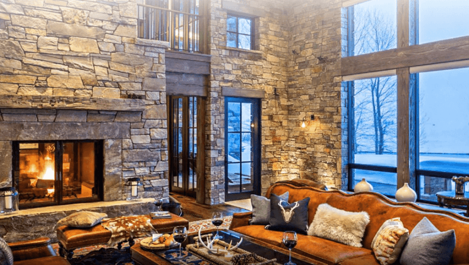Earth tone furniture and interior decoration surrounded by large stonework walls