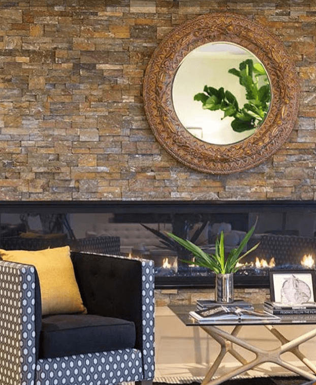 Chair covered in shapes and patterns in front of a stone wall and a linear fireplace
