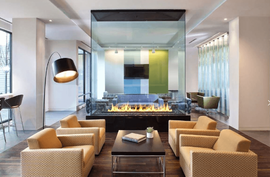 Home interior decorated with warm colors surrounding a tall see through fireplace