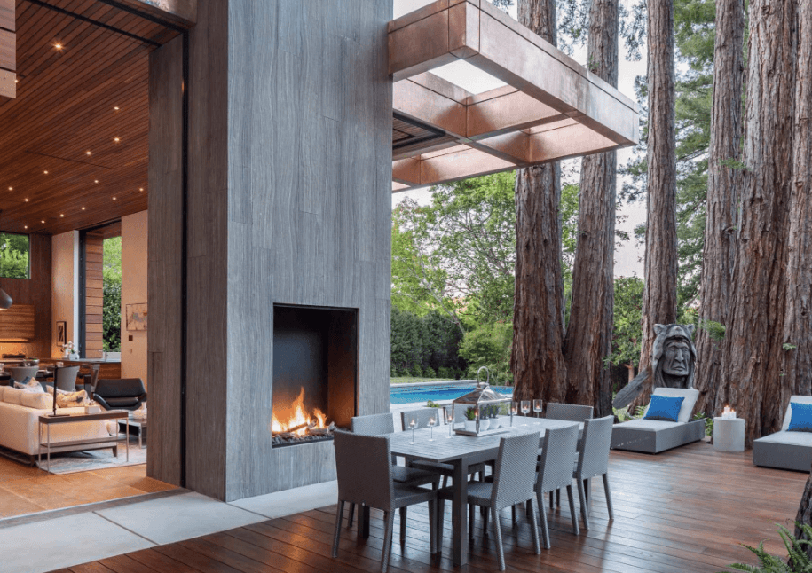 Large outdoor patio surrounded by tall trees with an open outdoor fireplace in the middle