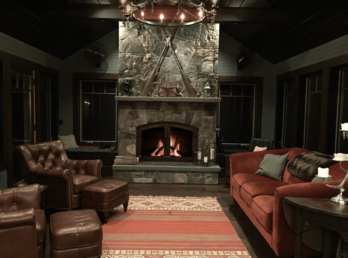 A dark living room filled with plush, dark furniture oriented around a stonework fireplace