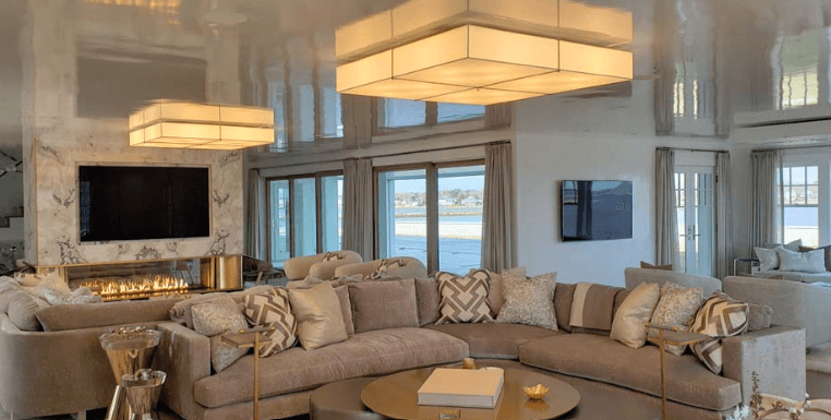 Large sectional sofas seated in front of a large tv and a linear fireplace