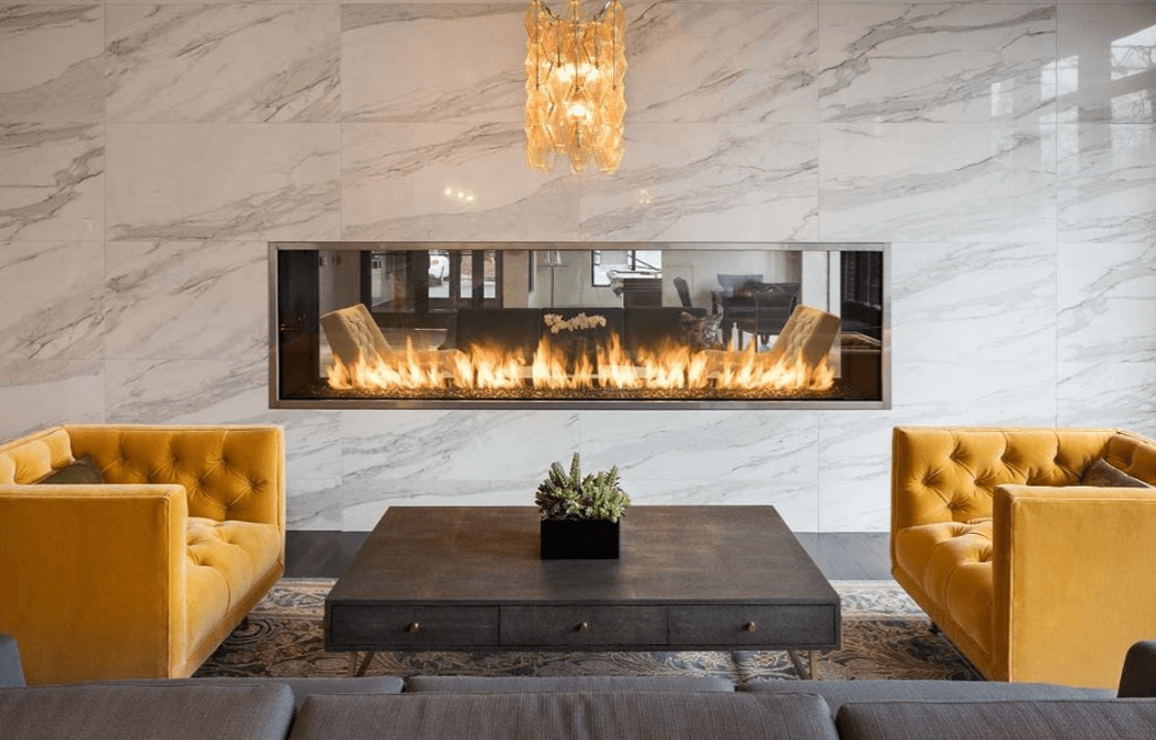 Gray couch and yellow chairs placed around a coffee table with a marble wall featuring a see-through linear fireplace in the background