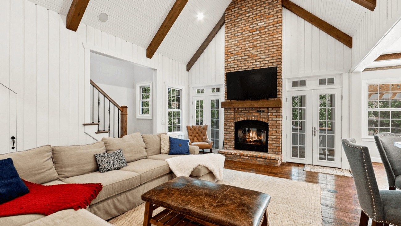 indoor/outdoor wood burning fireplace from the view of the living room in a nice large white living room