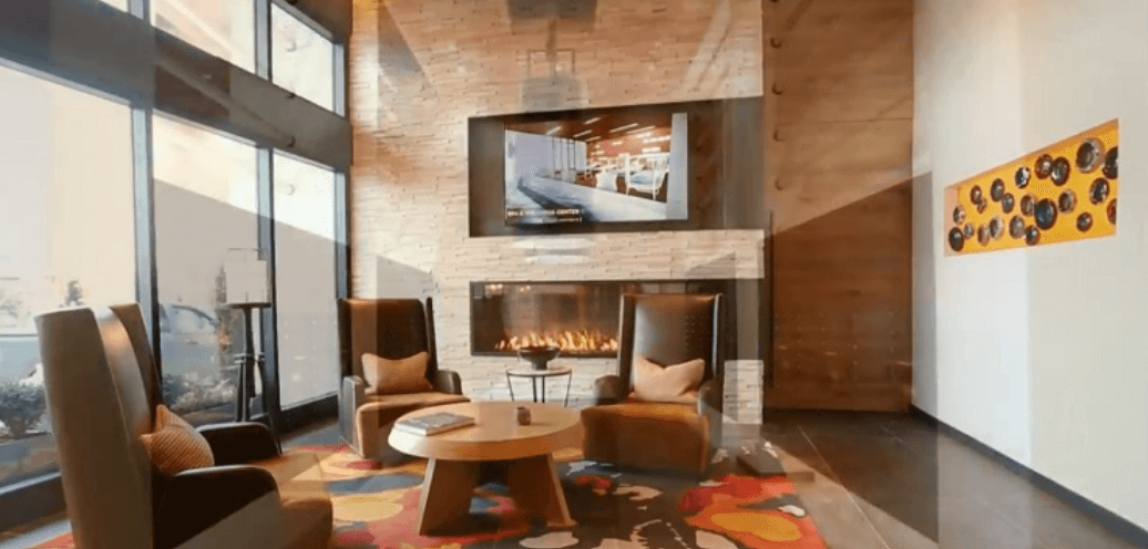 Warm color home interior with a TV mounted on the wall and a panoramic fireplace