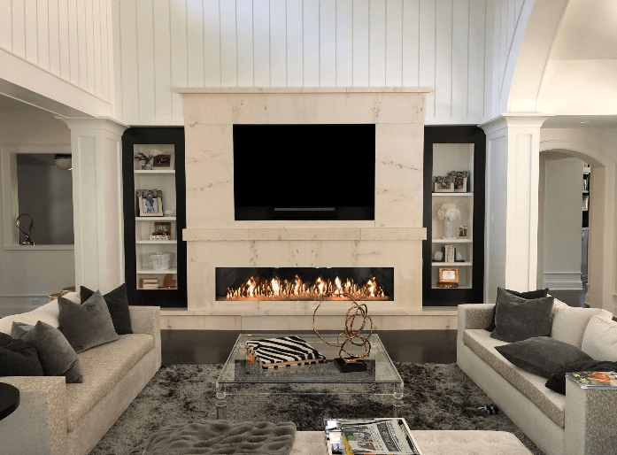 Beautiful living room centered around a marble entertainment center over a linear fireplace