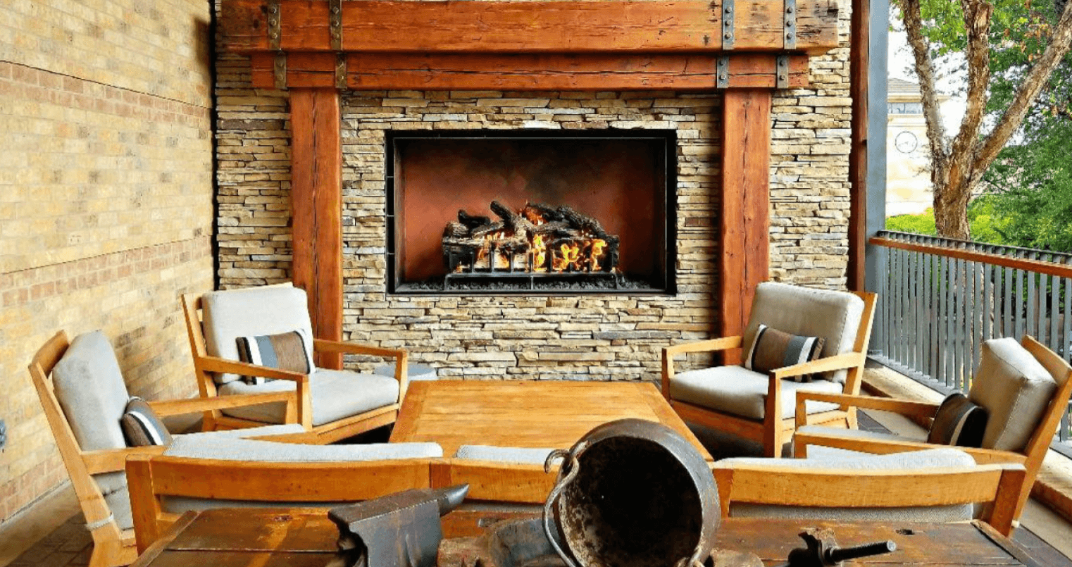 Gas fireplace outdoors with stonework surrounding the fire