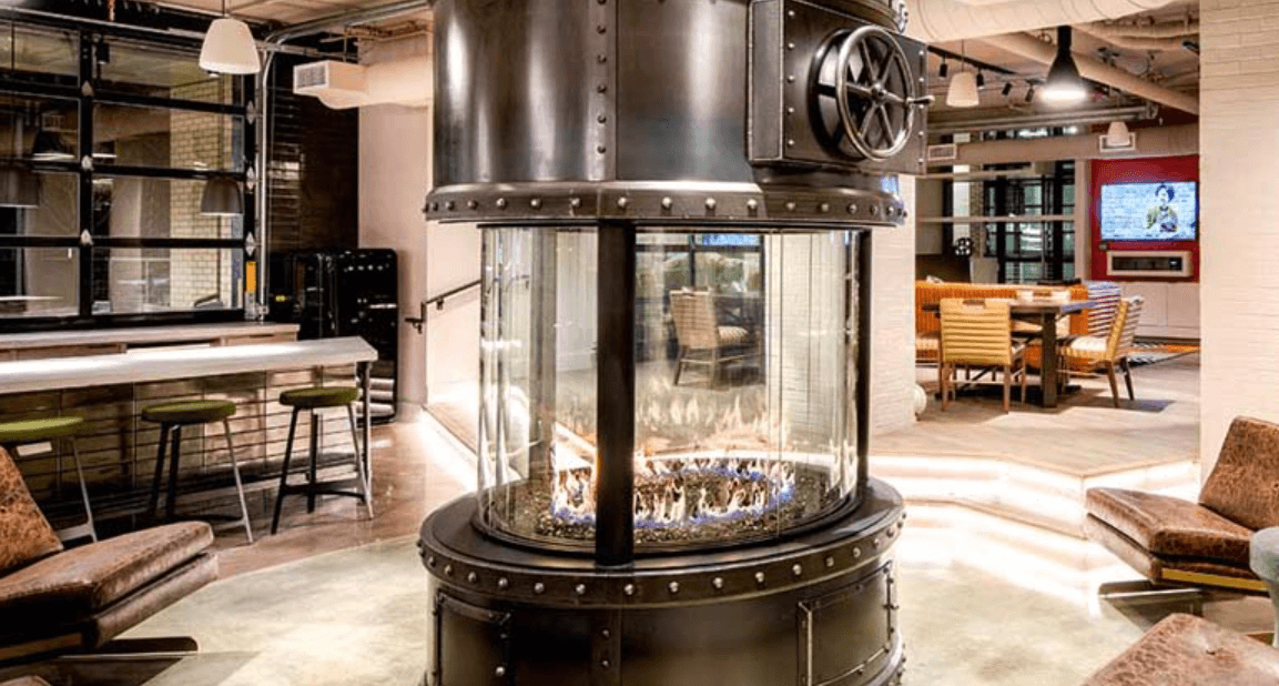 Round gas fireplace in a home with chairs surrounding it