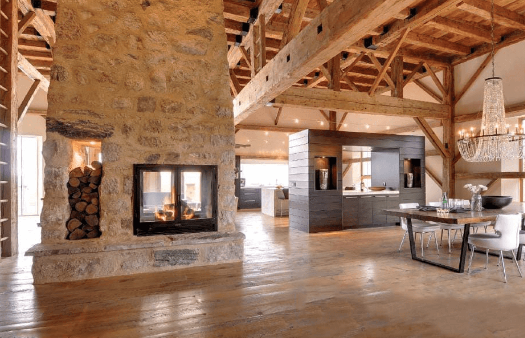 See-through fireplace in a large open home with wood floors and stone walls