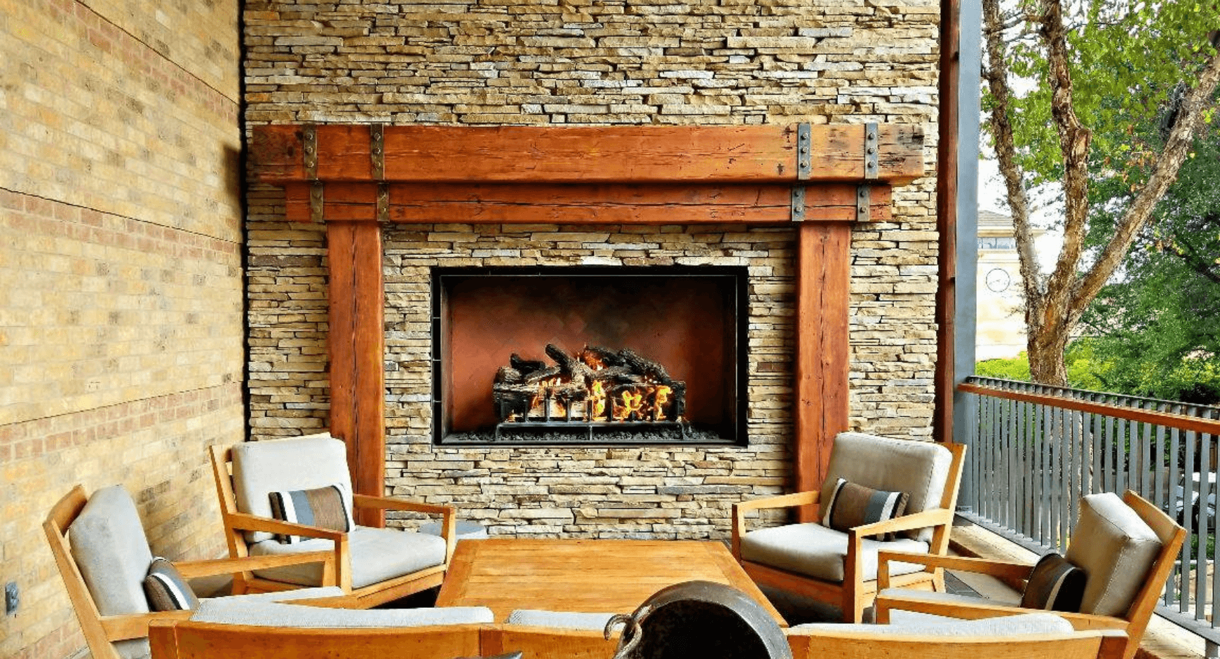Stacked stone veneer fireplace on a hotel deck gathering space