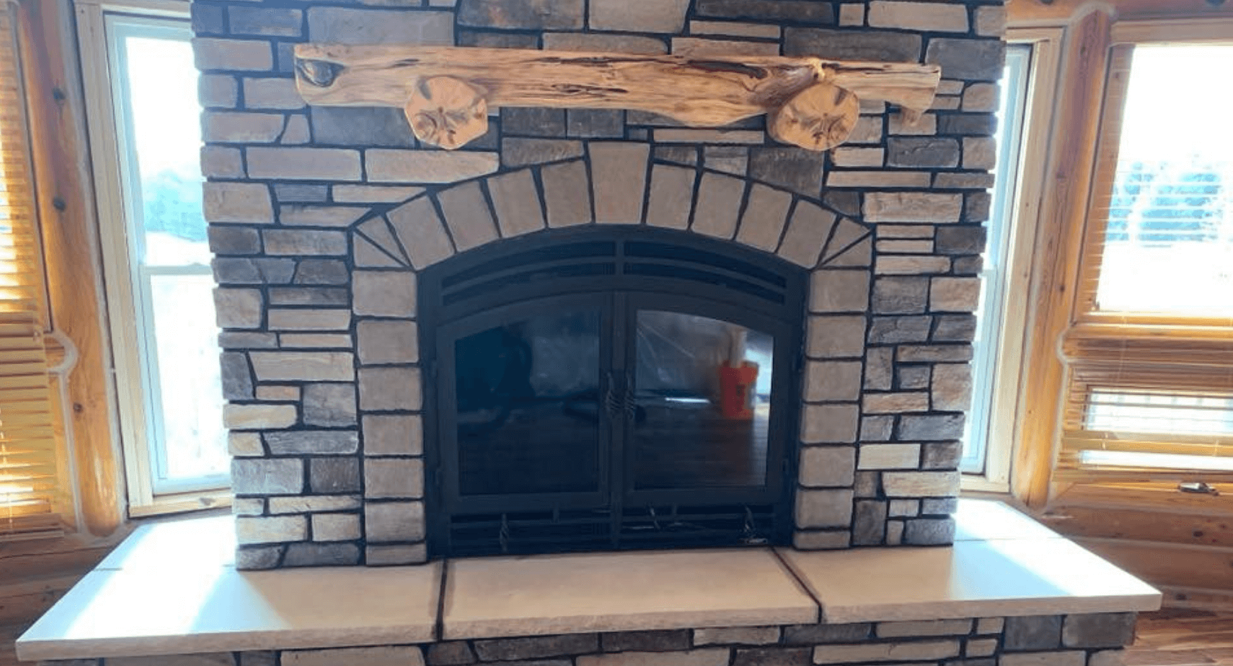 Clean stone fireplace with black doors and dark mortar