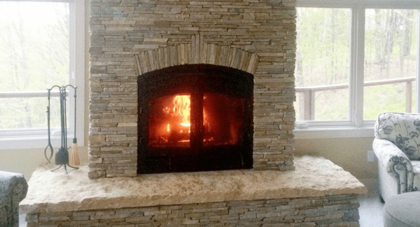A lit fireplace surrounded by thin stacked stone