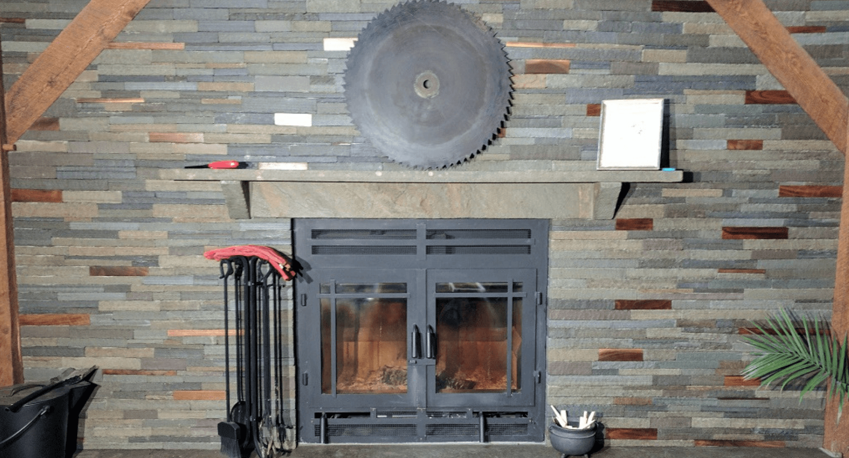 Iron door fireplace with stacked stone and stone mantle